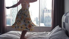 Young happy woman in dress jumping on hotel bed. slow motion. 3840x2160 stock video footage