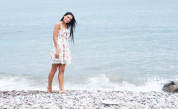 A young and happy woman in a dress near the sea Royalty Free Stock Photo