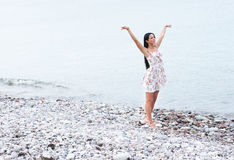 A young and happy woman in a dress near the sea Stock Images