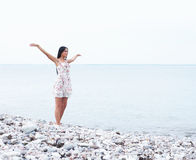 A young and happy woman in a dress near the sea Stock Photography