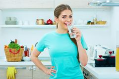 Young happy woman drink water standing in kitchen Stock Photo
