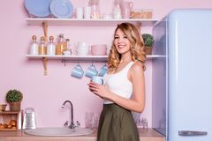 Young happy woman drinking coffee or tea at home in the kitchen. Blonde beautiful girl having her breakfast before going royalty free stock images
