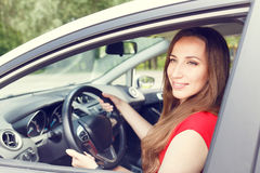 Young happy woman driving a new or rented car Royalty Free Stock Photos