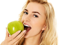 Young happy woman eating fresh green apple.  Stock Images