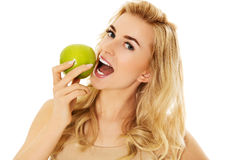 Young happy woman eating fresh green apple.  Stock Photo