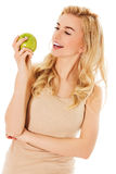 Young happy woman eating fresh green apple.  Royalty Free Stock Images