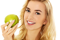 Young happy woman eating fresh green apple.  Royalty Free Stock Photos