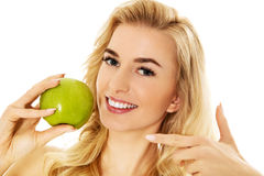 Young happy woman eating fresh green apple.  Royalty Free Stock Photography