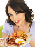 Young Happy Woman Eating a Full English Breakfast Royalty Free Stock Photography
