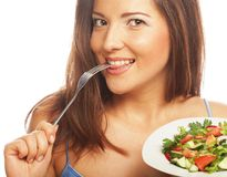 Young happy woman eating salad. Stock Photo