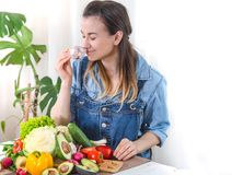 Young and happy woman eating salad at the table royalty free stock images