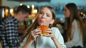 Young happy woman eating tasty fast food burger in cafe.  stock video footage