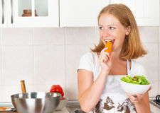 Young happy woman eats vegetable salad on kitchen Royalty Free Stock Photos