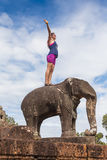 Young happy woman on elephant in the Angkor Wat temple. Stock Image