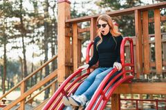 Young happy woman enjoying on the slide in the playground stock photo
