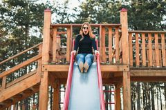 Young happy woman enjoying on the slide in the playground royalty free stock photos