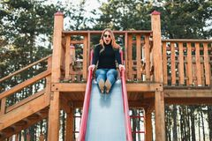 Young happy woman enjoying on the slide in the playground stock photos
