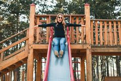 Young happy woman enjoying on the slide in the playground royalty free stock image