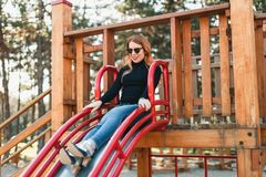 Young happy woman enjoying on the slide in the playground stock photography