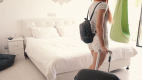 Young happy woman enters with a suitcase in her hotel room. Young happy woman enters with a suitcase into her new apartment, rear view stock footage