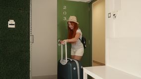 Young woman enters with her suitcase into her new apartment. Young happy woman enters with a suitcase in her hotel room stock footage