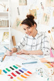 Young happy woman fashion illustrator drawing. Photo of young happy woman fashion illustrator sitting at the table and drawing. Looking at camera stock photos