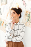 Young happy woman fashion illustrator. Image of young happy woman fashion illustrator standing near a lot of illustrations. Looking at camera Stock Photo