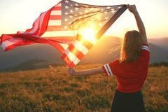 Happy woman with flag of united states enjoying the sunset on na. Young happy woman with flag of united states enjoying the sunset on nature royalty free stock photos