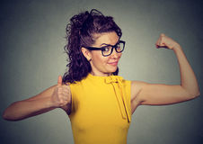 Young happy woman flexing muscles showing thumbs up. Isolated on gray background. Positive emotion facial expression. Weight loss wellbeing concept Royalty Free Stock Image