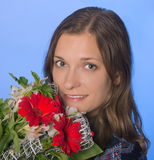 Young happy woman with flowers on blue background Royalty Free Stock Photo
