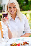 Young happy woman with glass of redwine. Young beautiful blonde woman drinking red wine Stock Photography