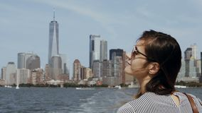 Young happy woman go for a boat through the East river in New York, America, looking on Manhattan and enjoying. stock video
