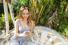 Young happy woman hatting by smartphone with palms in background, sitting on swing. royalty free stock photography
