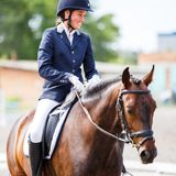 Young happy woman on her horse after dressage test Royalty Free Stock Photo