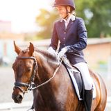 Young happy woman on her horse after dressage test Stock Photo