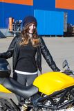 Young happy woman with her new just delivered motorcycle in freight company, receiving a bike Stock Image