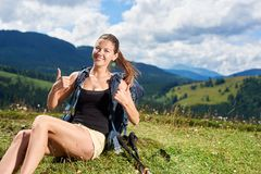 Woman hiker hiking on grassy hill, wearing backpack, using trekking sticks in the mountains. Young happy woman hiker hiking in Carpathian mountain trail, showing stock photos