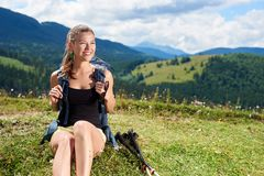 Woman hiker hiking on grassy hill, wearing backpack, using trekking sticks in the mountains. Young happy woman hiker hiking in Carpathian mountain trail, sitting royalty free stock image