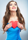 Young happy woman hold Love symbol red heart. Isolated on studi Stock Image