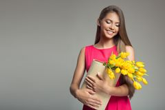 Young happy woman holding basket with yellow tulips. Royalty Free Stock Photography