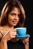 Young happy woman holding blue tea cup and saucer Royalty Free Stock Images