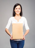 Young and happy woman holding a box on grey Stock Photography