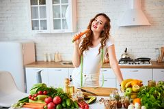 Young happy woman holding carrot in the beautiful kitchen with green fresh ingredients indoors. Healthy food and Dieting concept. Young happy woman holding stock images