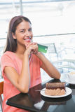 Young happy woman holding credit card and a cake in front of her Stock Photography