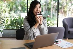 Happy woman holding a credit card and using laptop computer for Stock Photo