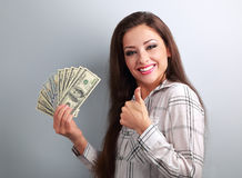 Young happy woman holding dollars and showing thumb up sign on b Royalty Free Stock Image