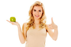 Young happy woman holding fresh green apple.  Royalty Free Stock Images