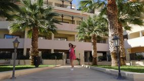 Young happy woman holding her hat wearing red dress walking towards camera and spinning around posing with palm trees on the backg. Round stock video