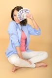 Young Happy Woman Holding Money Looking Pleased and Delighted. A DSLR royalty free image, of attractive relaxed happy young woman sat on the floor with crossed Royalty Free Stock Photos