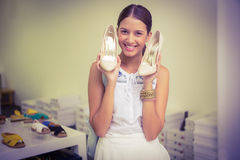 Young happy woman holding a pair of shoes in her hand while looking at t he camera Stock Photography
